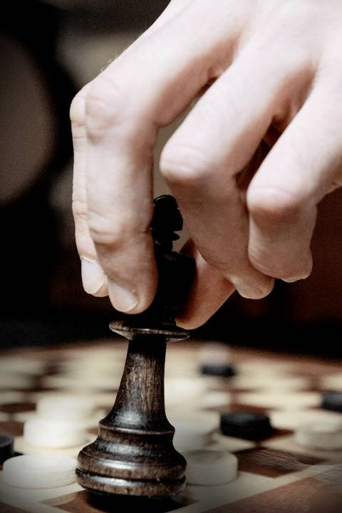 Chess board with a piece in a person's hand